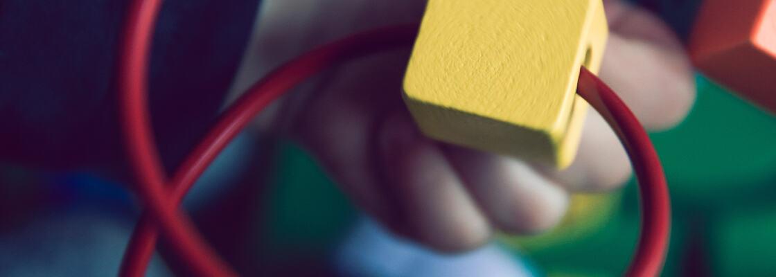 Et barn leker med geometriske former i et stativ. Foto