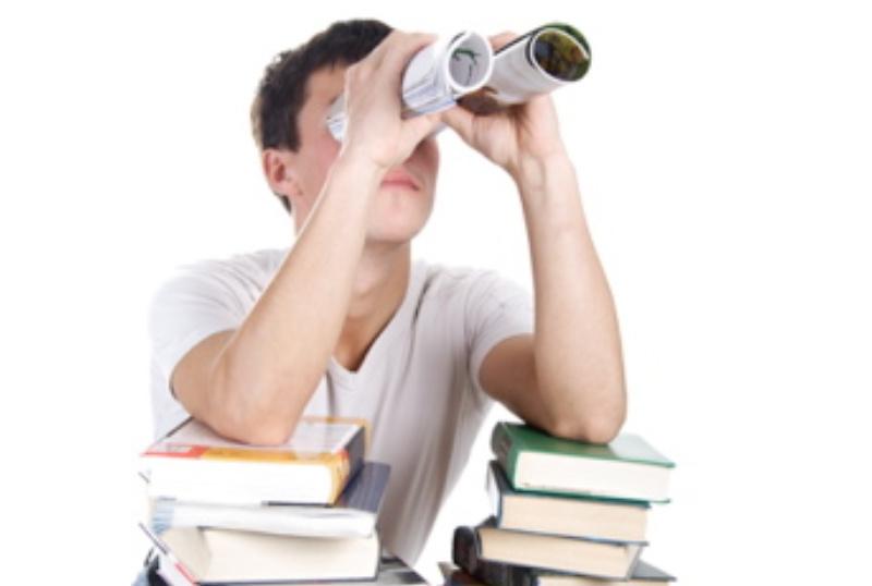 Student med mange bøker og kikkert av rullet papir