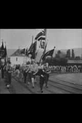 Bilde fra filmrullen Norsk films revy nr.3, 1941. Sorthvittbilde med medlemmer fra Nasjonal samling som marsjerer med norske flagg. Bildet har et sort felt i over- og nedkanten, som viser at det er klipt fra en filmrull.